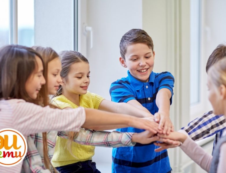 group of smiling school kids putting hands on top